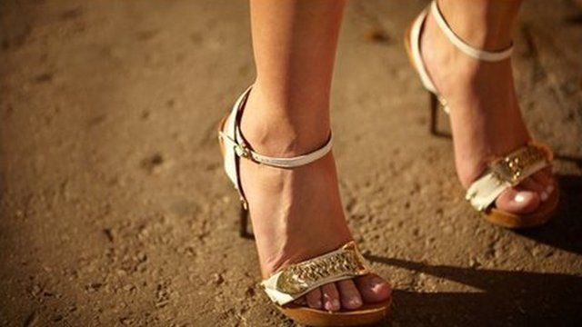 The feet of a woman wearing high heels