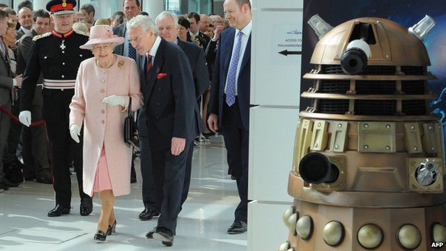 The Queen walks through MediaCity reception towards a Dalek