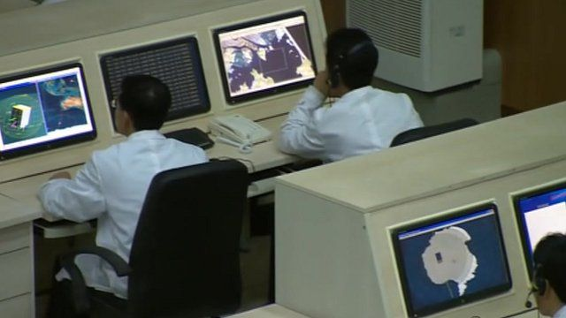 Men looking at computers inside North Korea's mission control
