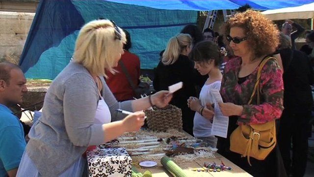 Woman hands over 'exchange' paper at bartering market.
