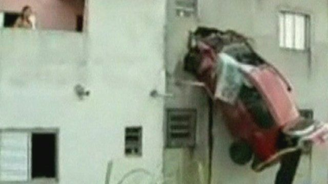 Car stuck on side of building