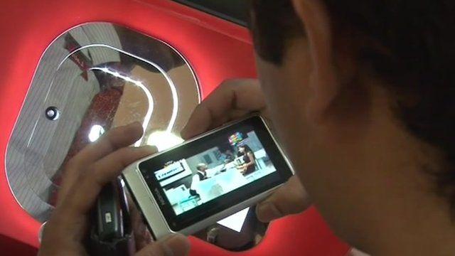 Man using hand-held TV screen