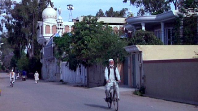 A man rides a bicycle along a road in Peshawar