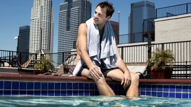 man sitting by side of roof swimming pool