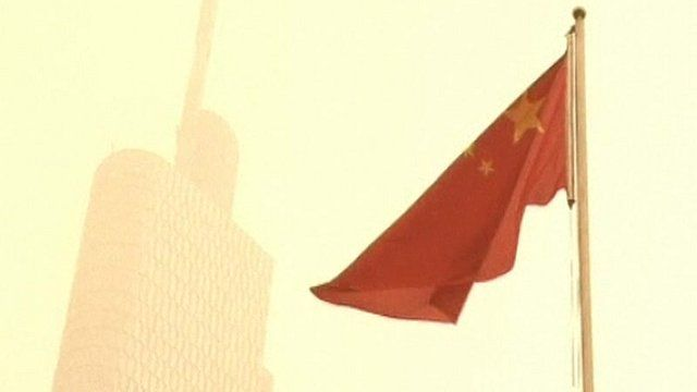 A smoke covered building behind a Chinese flag