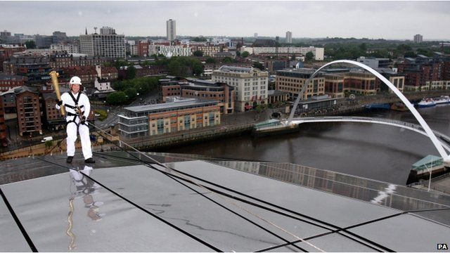 Richard Jackson abseils down the Sage Gateshead with the Olympic flame