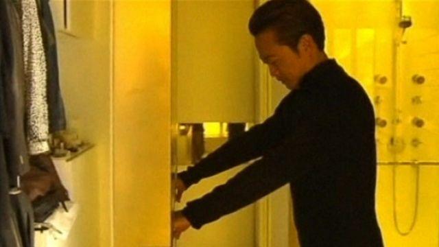 Architect Gary Chang pushing a wall in his flat.