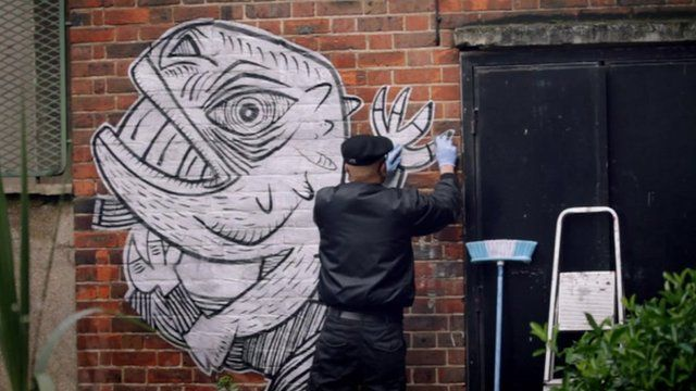 A mural being put on a wall in Dalston
