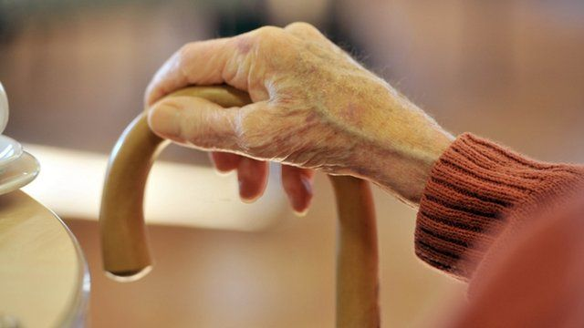 Elderly person with walking stick