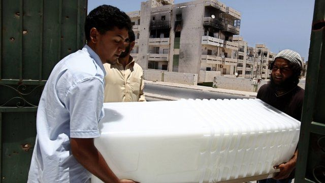 Volunteers carry ballots boxes into a voting centre in Libya