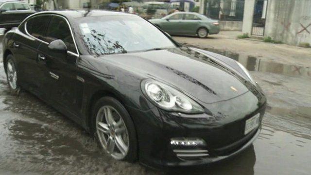 A sports car drives through a puddle in Lagos, Nigeria