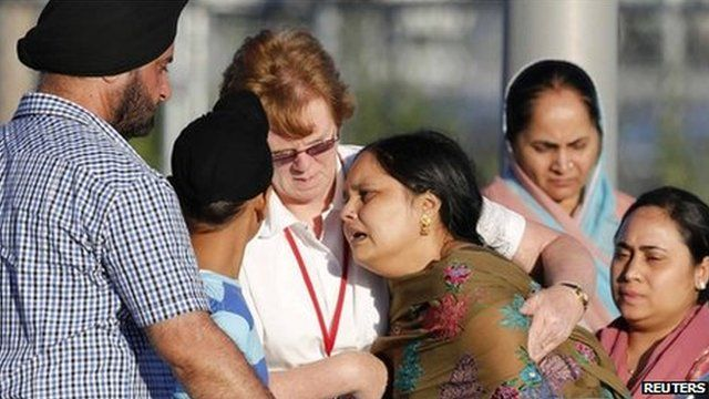 A distraught women is helped to a car outside of the Sikh temple in Oak Creek, Wisconsin