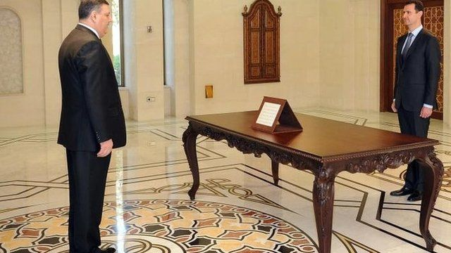 Syrian news agency picture of former Prime Minister Riad Hijab (L) being sworn in on 26 June in front of President Assad