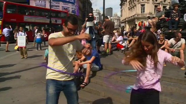 Tourists try their hand at rhythmic gymastics in central London