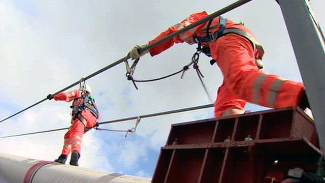 People in safety harnesses inspect the Forth Road Bridge
