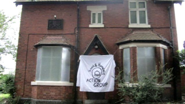 A house with boarded windows and a homeless action group flag outside