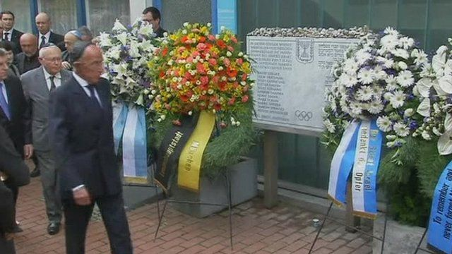 Flowers and wreaths were laid at a plaque in the Olympic Village