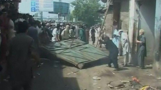 Protesters attacking a cinema in Peshawar