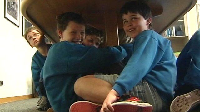 Boys sheltering under a table
