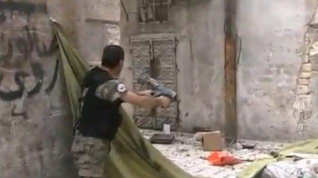 Man shooting round corner of building