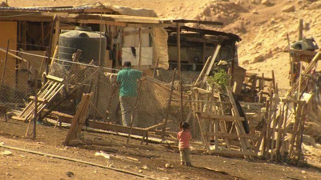 Bedouin villagers by their home