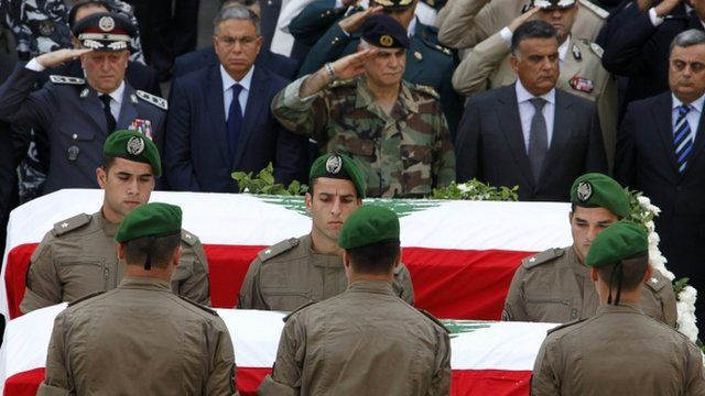 Members of the Internal Security Forces lay the coffins of slain intelligence officer Wissam al-Hassan and his bodyguard Ahmed Sahyouni