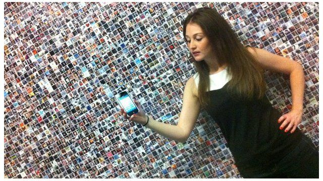 Employee of Mashable holding a mobile phone in front of faces on a wall