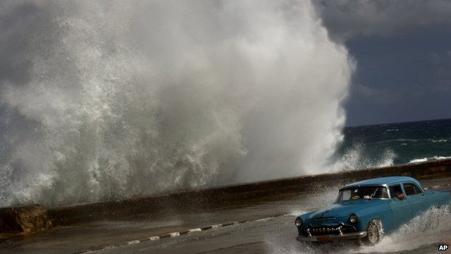 A driver maneuvers along a wet road as a wave crashes against the Malecon in Havana