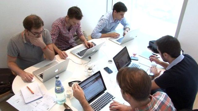 Workers around table on laptops