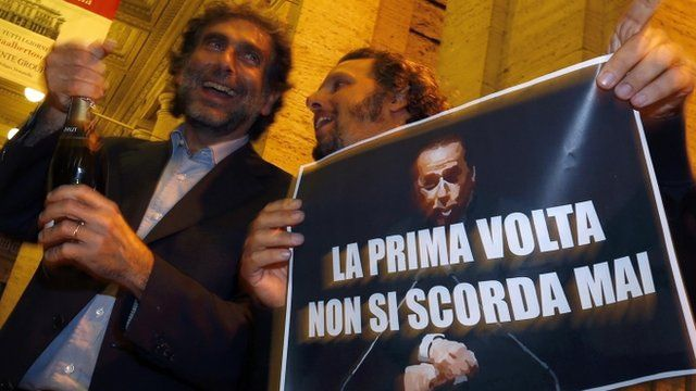 """People hold a picture of Italy""""s former PM Berlusconi with words that read """"You Never Forget Your First Time"""" as they celebrate after Berlusconi was sentenced to jail for tax fraud in downtown Rome"""