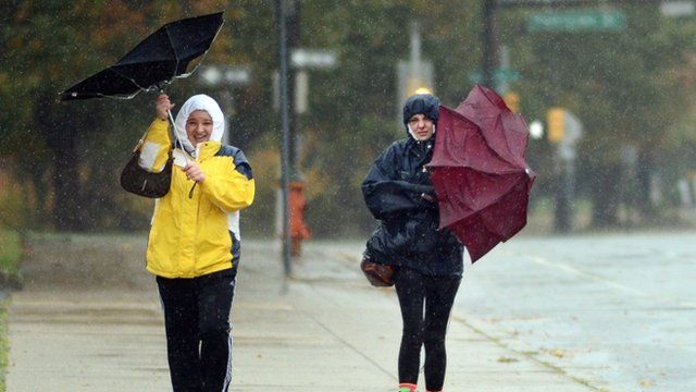 Two women try to hold on to their umbrellas in a wind soaked rainfall as Hurricane Sandy approaches October 29, 2012 in Philadelphia, Pennsylvania.