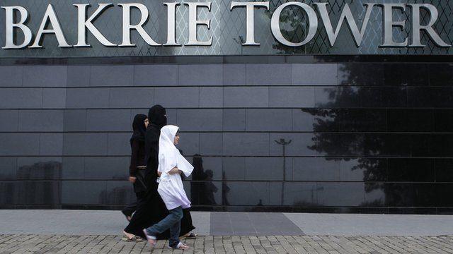 Women walk in front of the Bakrie Tower in Jakarta