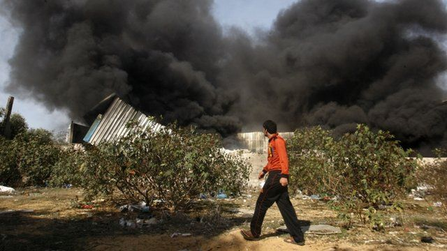 A man walks past a fire after an Israeli airstrike on a wood factory north Gaza