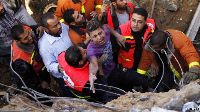 A man being saved after his house was destroyed in an Israeli air strike, Gaza City, 18 Nov 2012
