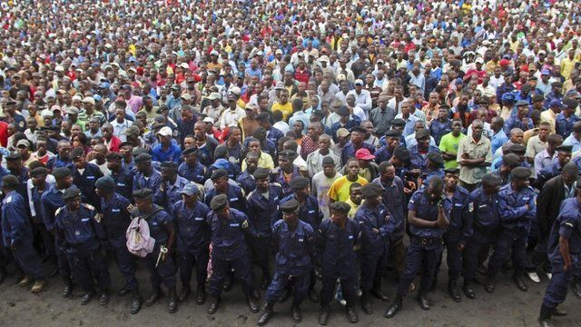 Congo government policemen, foreground, and civilians gather during a M23 rally in Goma, DR Congo