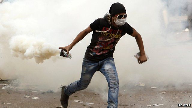 Protester holding a teargas canister