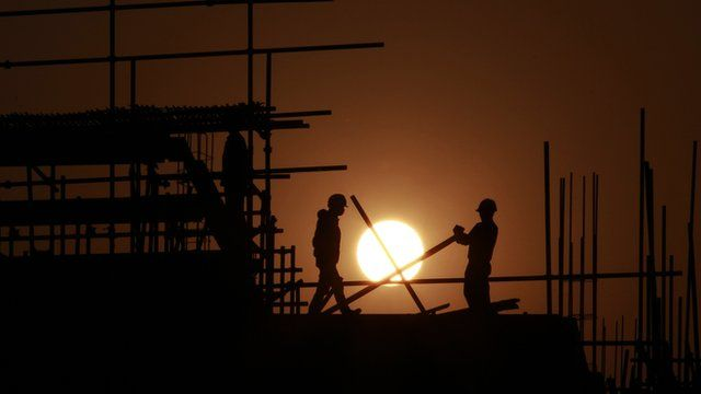 Construction workers install scaffolding on a building at sunset in Shanghai