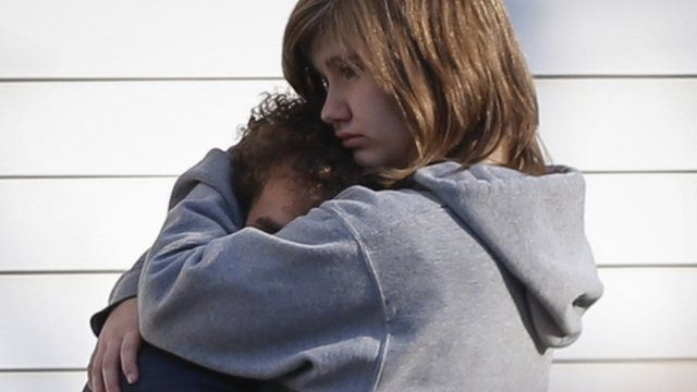 A couple embrace outside Sandy Hook school in Newtown, Connecticut