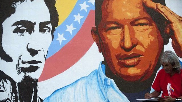 An artist draws next to a painting of Venezuelan President Hugo Chavez in Caracas, on 3 January 2013