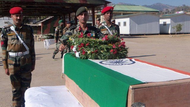 Indian Army officers laying a wreath on a coffin