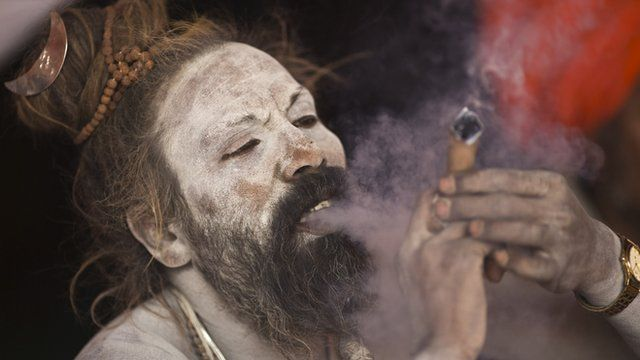 A Sadhu smokes marijuana on the banks of river Ganges
