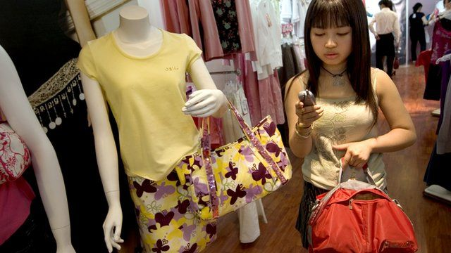 Chinese woman using mobile phone in a department store in Beijing