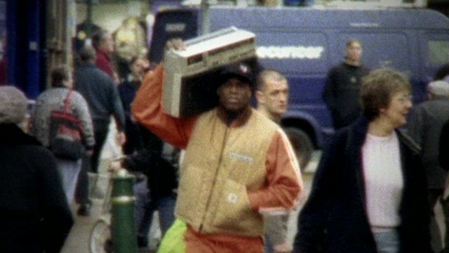 Man carrying a portable cassette player on his shoulder