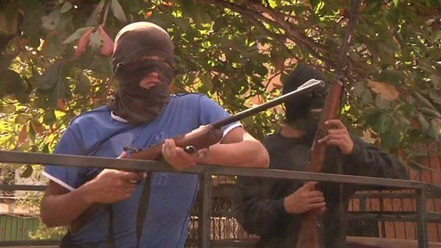 Men in masks holding guns