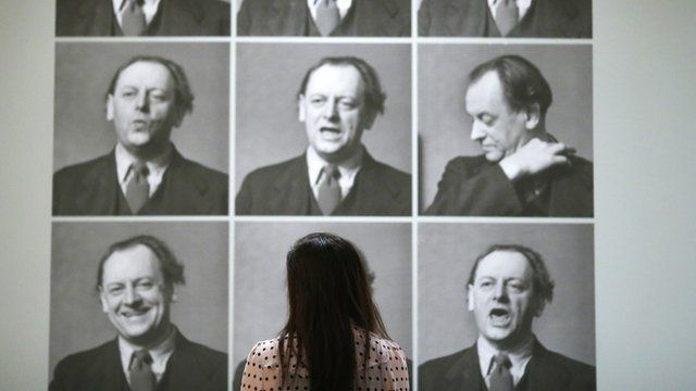 A worker poses next to photographs of Kurt Schwitters