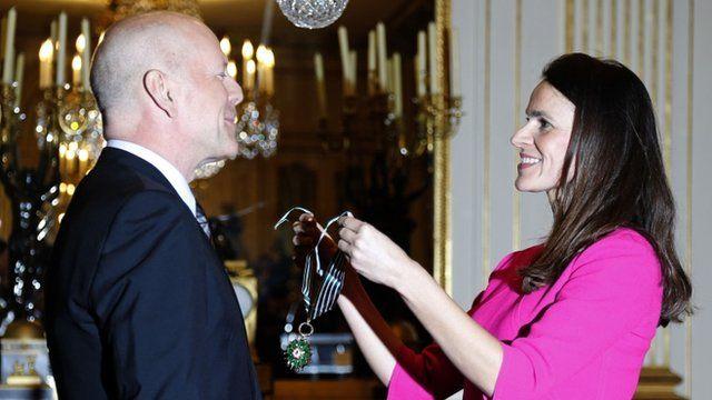 Bruce Willis receiving award from Culture Minister Aurelie Filippetti