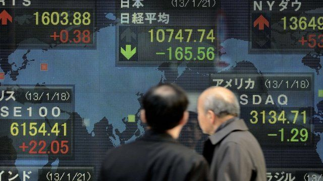Men look at an electric quotation board flashing some key stock market indexes from around the world in front of a securities company in Tokyo on January 21, 2013.