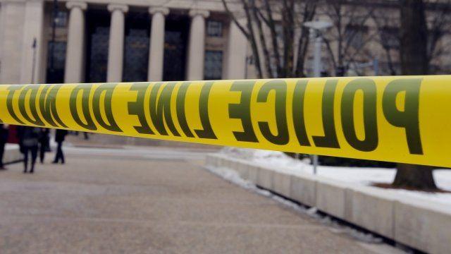 Police tape blocks a sidewalk