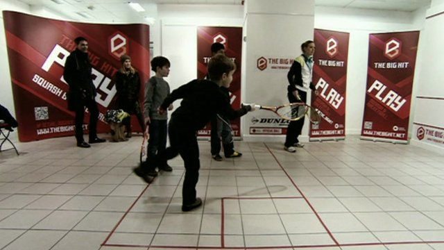Child plays squash inside a converted shop