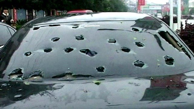 A car windshield punctured with hailstones